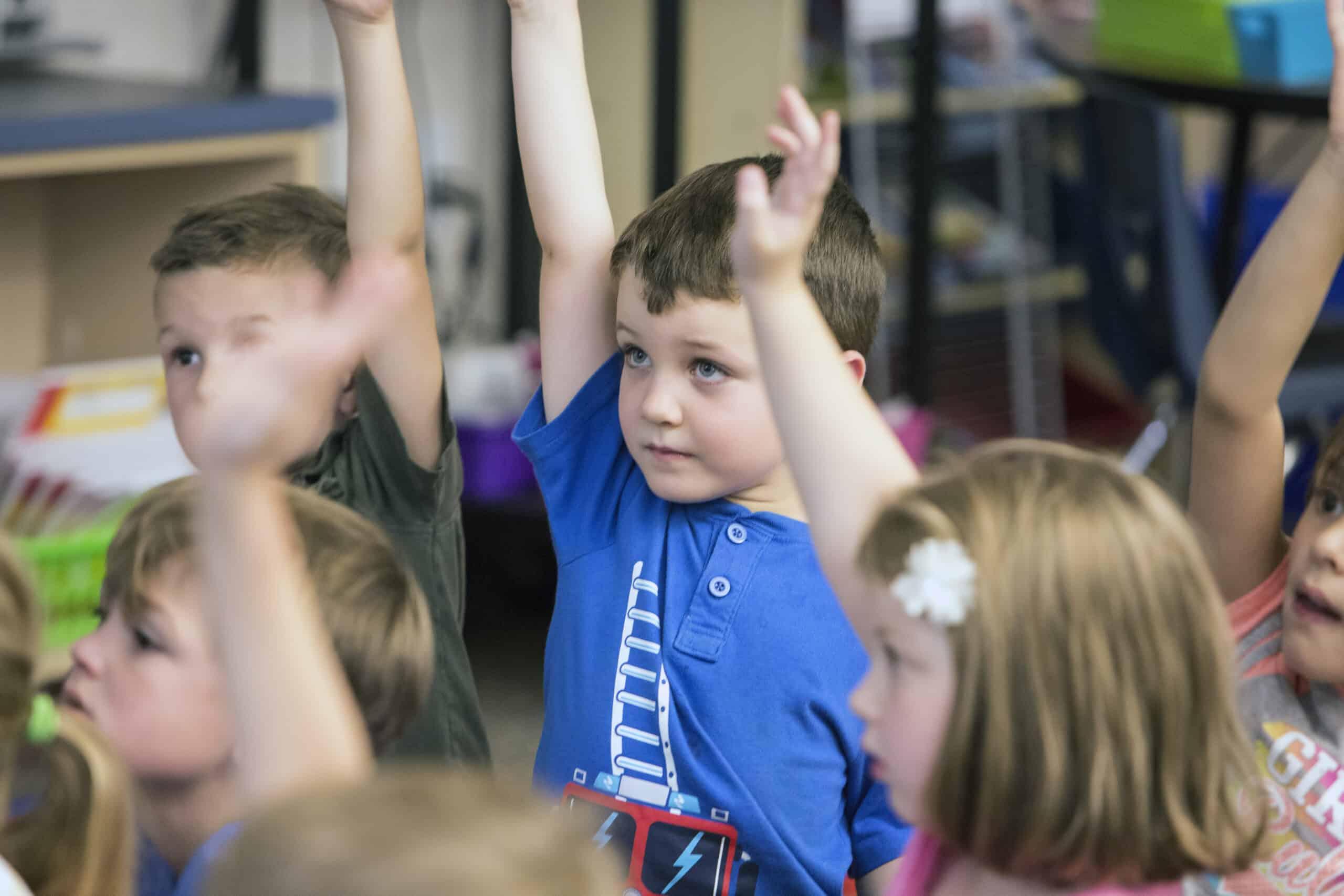 Alpine Elementary student raising his hand