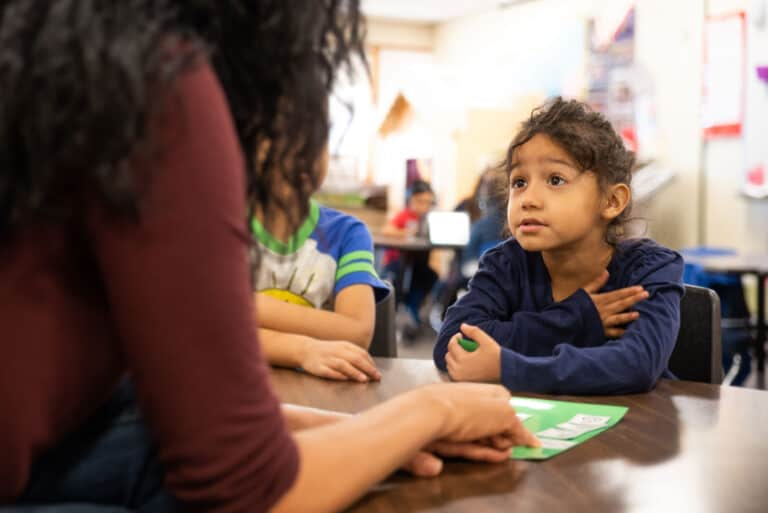 PreK student working with a teacher