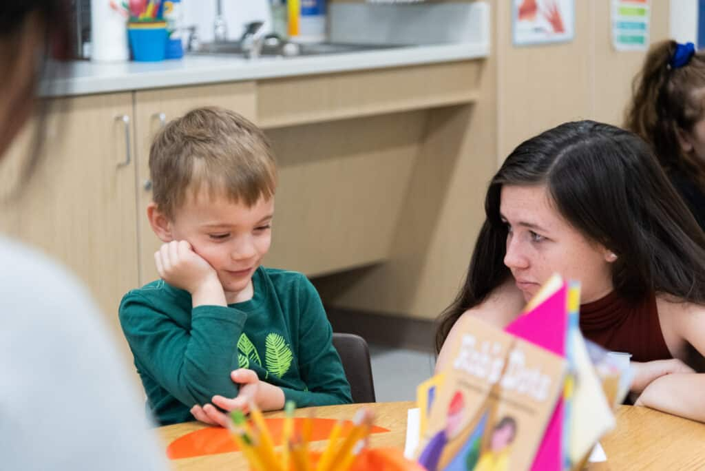 Middle school student interacting with a kindergarten student at a table