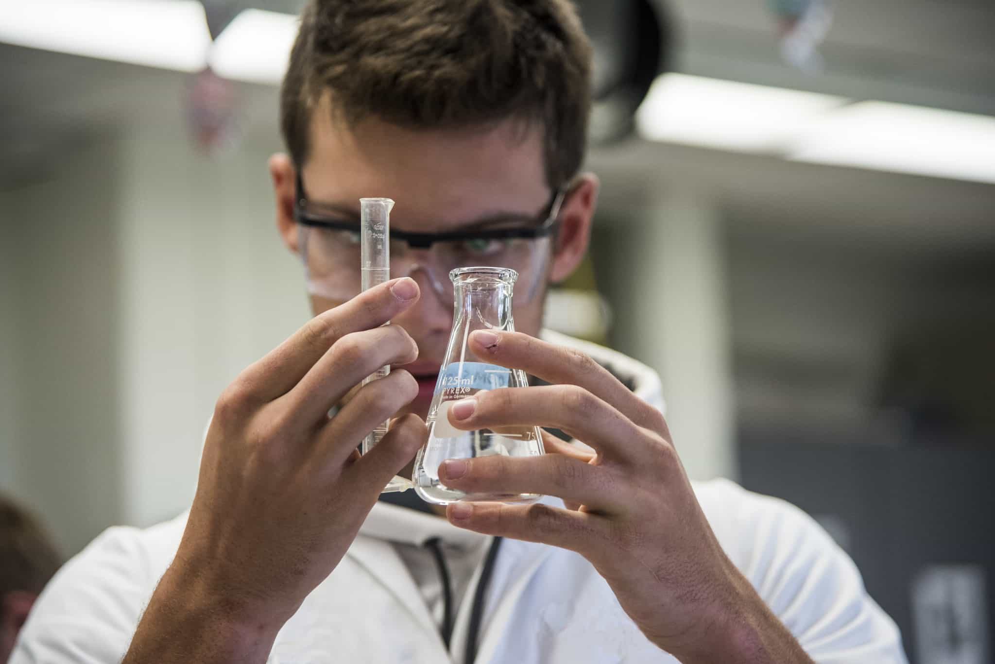 High school student holding glass beakers