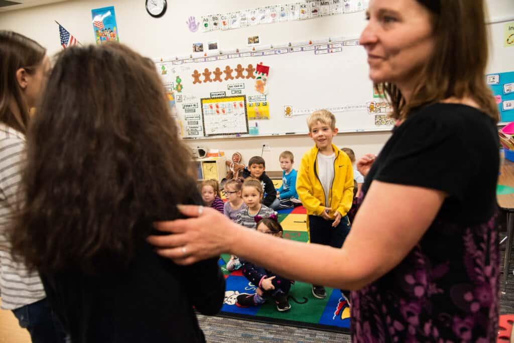 Teacher introducing middle school students and kindergarten students.