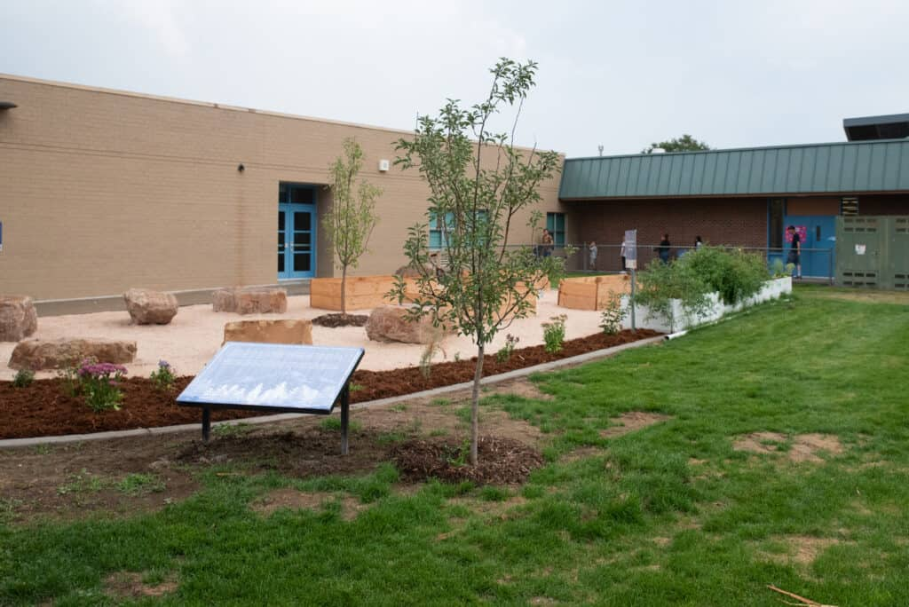 A picture of the outdoor classroom- green grass, red rocks.