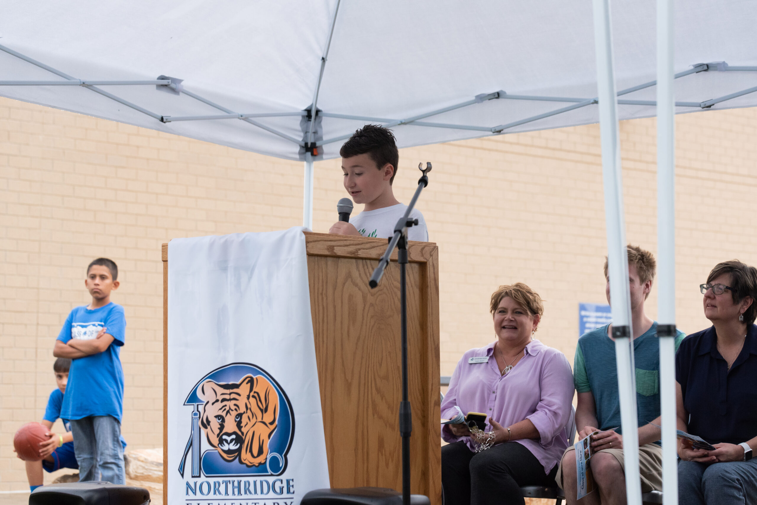 An elementary aged student speaking at a podium to open the new outdoor learning space.