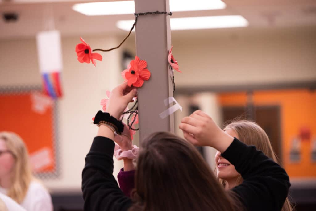 Students decorating for event, hanging flowers up on a light post.