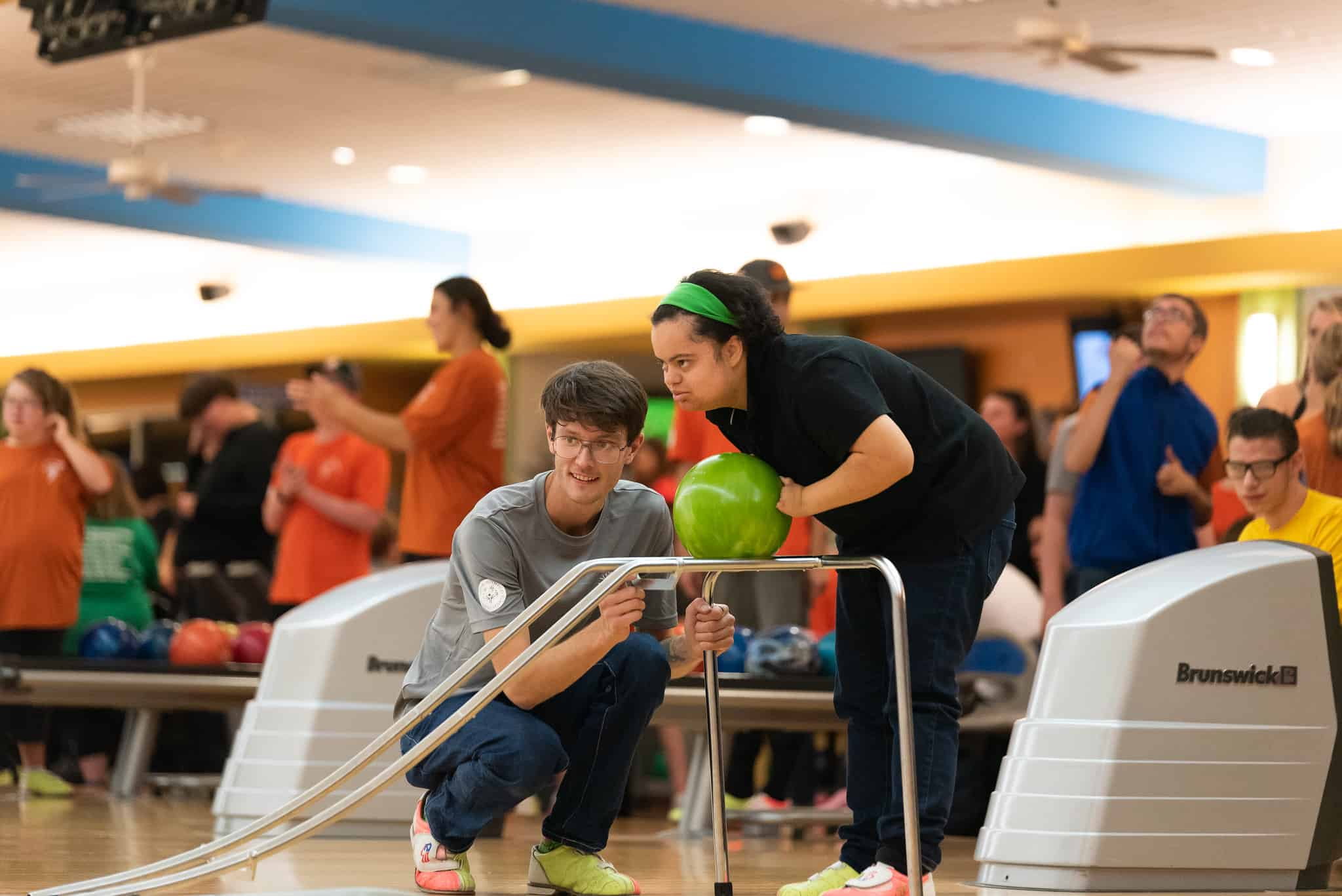 A student athlete and partner using a bowling ramp