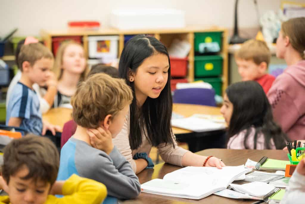 Middle school student reading to a kindergarten student at a table surrounded by students.