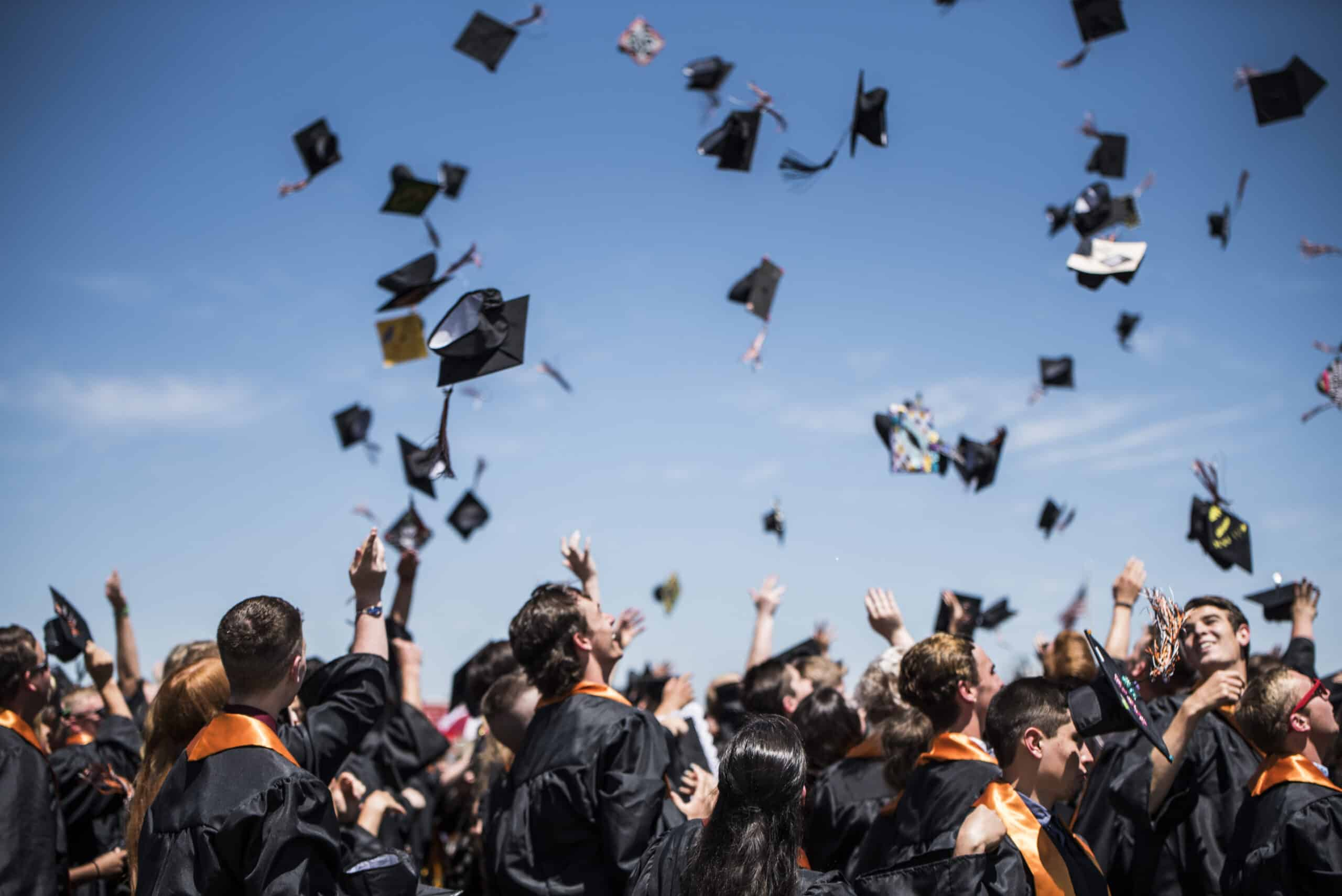 Students at high school graduation throwing their caps in the air