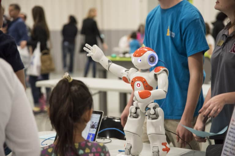 Elementary aged girl engaging with robot