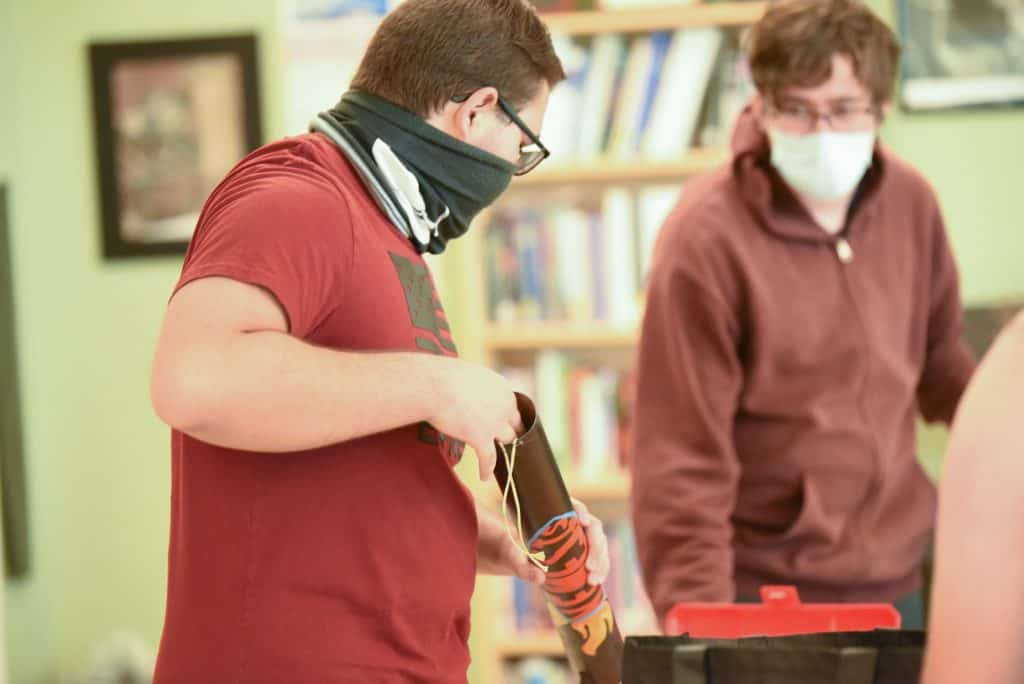 a male high school student in a red shirt and a face gaiter loads a parachute into a rocket inside a classroom