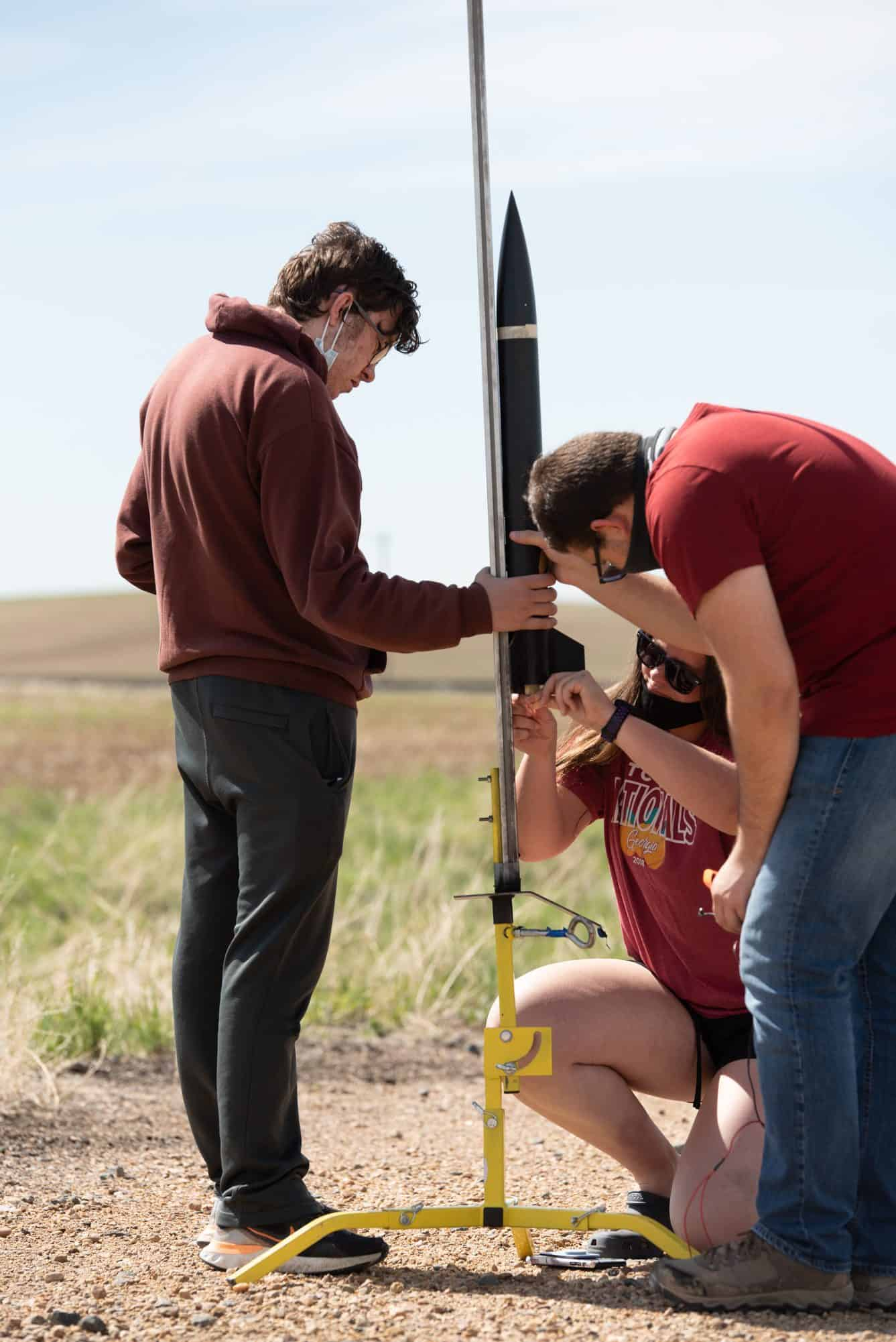 3 students gather and crouch around a rocket to prepare it to launch in a grassy field