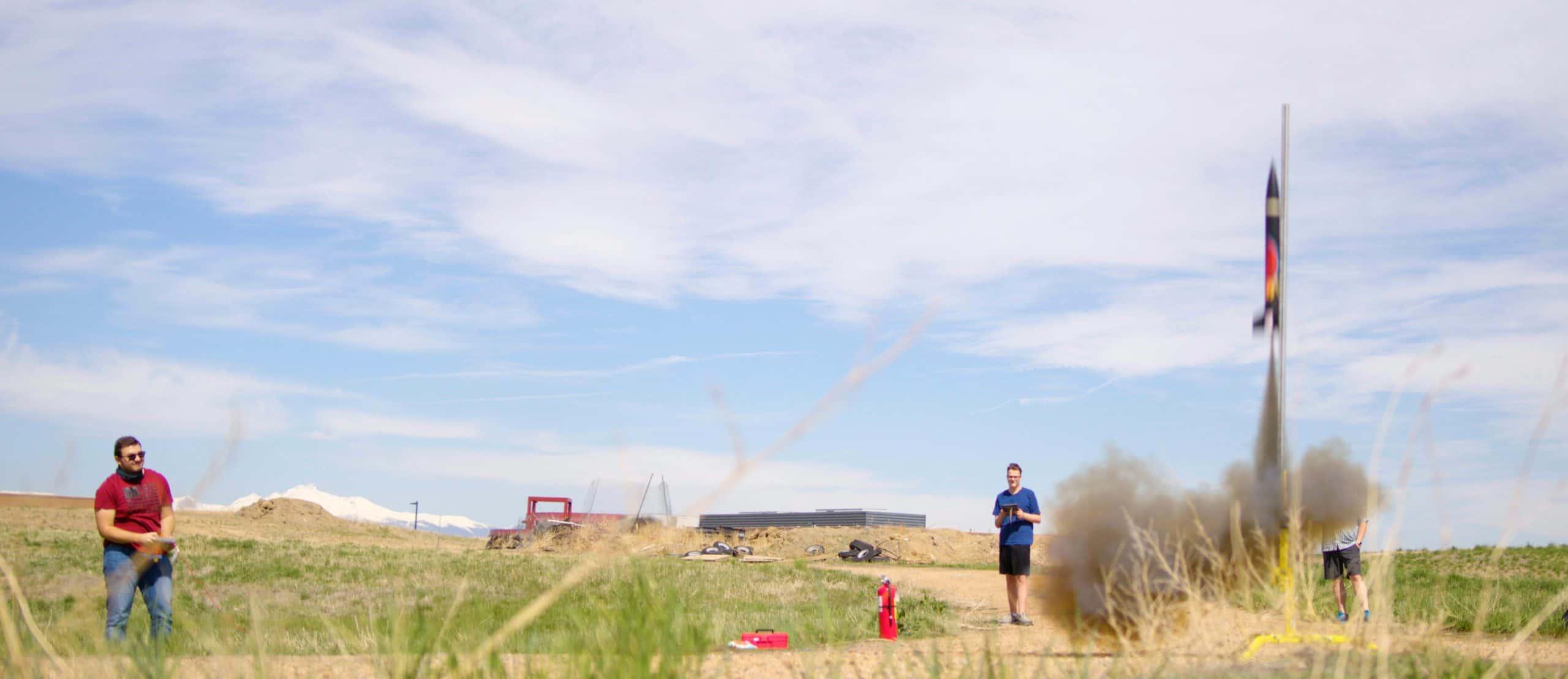 erie high school students launch a rocket in a field