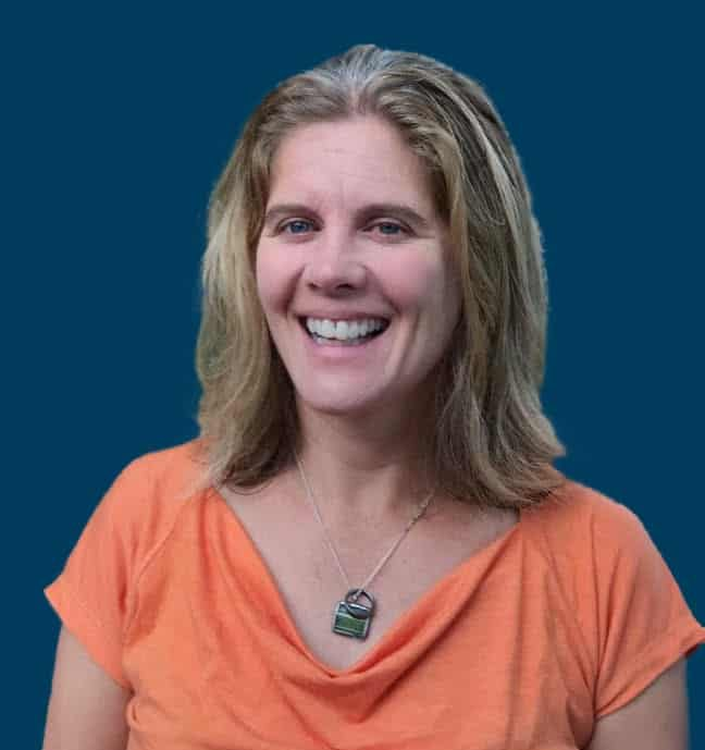 Nora Curtin smiling in front of a navy blue background.