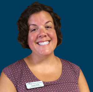 Laura Gold smiling in front of a navy blue background.