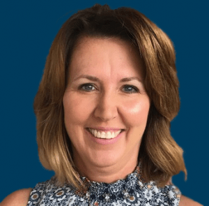 Kathy Oakes smiling in front of a navy blue background.